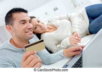 Couple shopping online paying by credit card