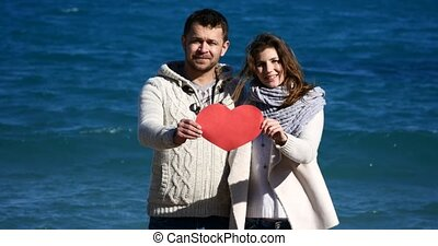 Couple showing heart shape red paper on the sea - Young...