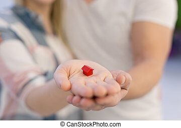 couple showing small red house in hands