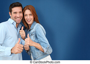Couple showing thumbs up on blue background