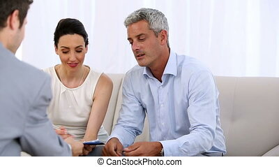 Couple signing a contract given by a salesman then giving a...