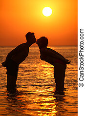 Couple silhouette kisses in sea on sunset