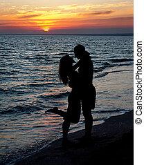 couple silhouette on beach against sunset