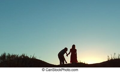 couple silhouette walking. slow motion video. holding hand toward the sun outdoors at sunset dramatic sky background and dog. young happy couple go on nature sunset sun light. man and girl silhouette love friendship at sunset concept run go and dog walking lifestyle