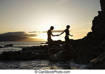 Couple silhouetted on beach. - Young adult Caucasian male...