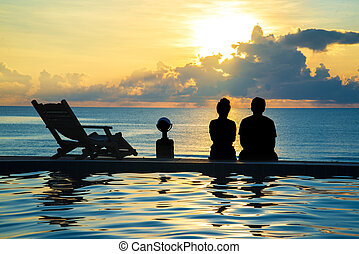 couple sit at swimming pool watching sunset at sea.