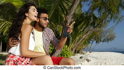 Couple Sit Embracing On Beach Under Palms Using Cell Smart...