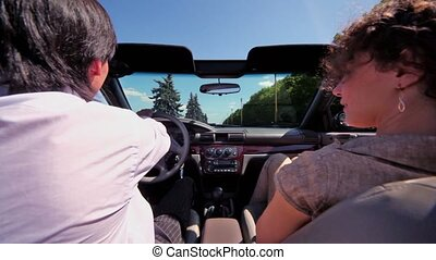 Couple sit in cabriolet and ride by road at sunny summer day