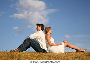 couple sit on meadow back to back
