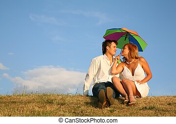 couple sit on the meadow under umbrella