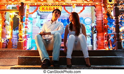 couple sits and talks at doorway - young couple sits and...