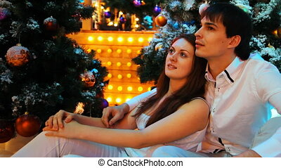 couple sits embracing near snowy Christmas trees and blinking lamps