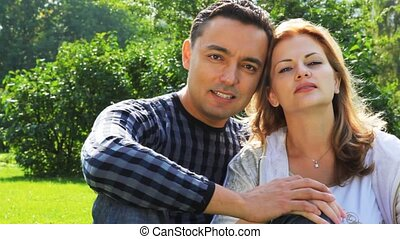 couple sits in park and look, woman with braces