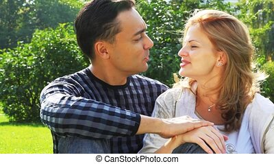 couple sits in park and talk, woman with braces