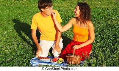 couple sits on green lawn and feed each other with fruit, vine and cherry