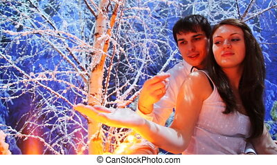 couple sits on lighted balcony in snowy birch forest at night