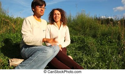 couple sits on log on green lawn and talks in park in summer