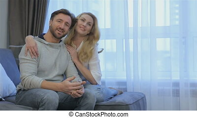 Couple sits on the couch at home