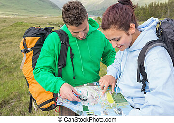 Couple sitting after hiking uphill and consulting map in the...
