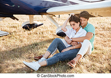 Couple sitting and embracing near private aircraft