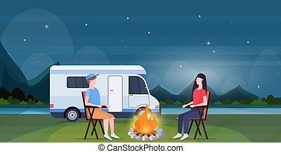 couple sitting around campfire at night near camping trailer truck caravan car man woman spendingtime togeher summer vacation concept beautful nature landscape background full length horizontal