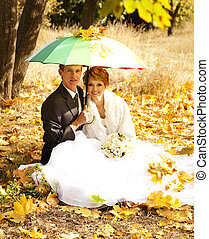 Couple sitting at the park with umbrella