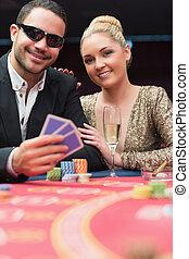 Couple sitting at the poker table smiling