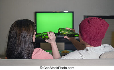 Couple sitting at the TV on the couch with bottles of beer, blurred background, green screen