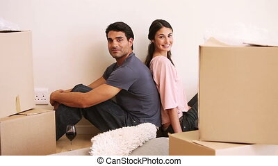 Couple sitting back to back in a room with boxes