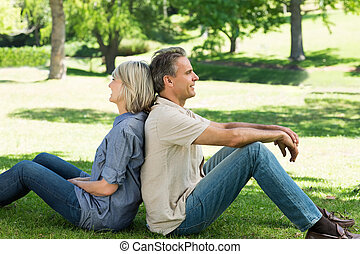 Couple sitting back to back in park