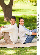 Couple sitting back to back in the park