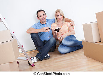 Couple Sitting Between Cardboard Boxes