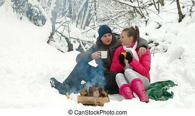 Couple Sitting by Bonfire in Winter