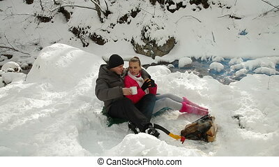 Couple Sitting by Bonfire in Winter