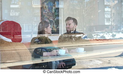 Couple sitting in a coffee shop and drinking coffee, the view through the window