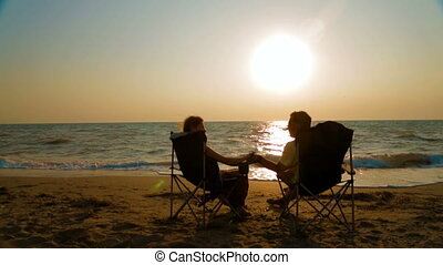Couple sitting in armchairs facing the sea