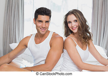 Couple sitting in bed at home