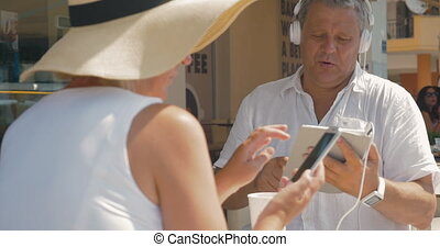 Couple sitting in cafe and using gadgets
