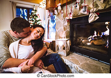 Couple sitting in front of fireplace, relaxing.