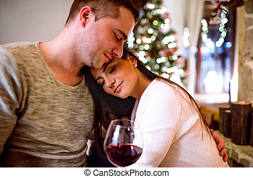 Couple sitting in front of fireplace, drinking wine.