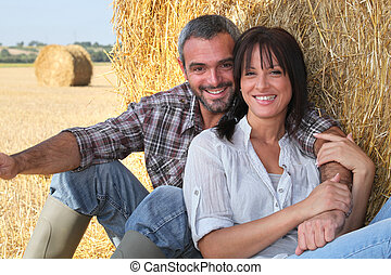 Couple sitting in front of hay bale