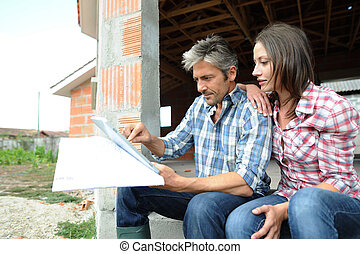 Couple sitting in house under construction