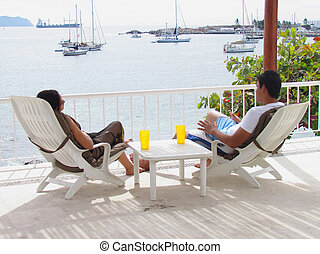 couple sitting in lounge chairs by the ocean
