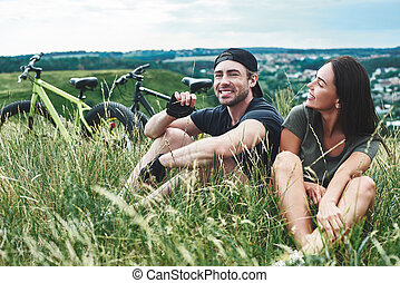 Couple sitting in the grass, romantic mood. Warm season