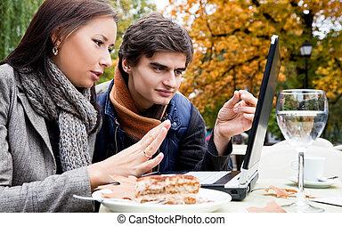 Couple sitting laptop park