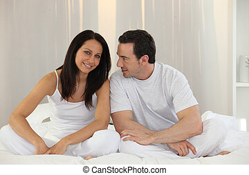 Couple sitting on a bed