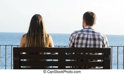 Couple sitting on a bench and relaxing - Back view portrait...