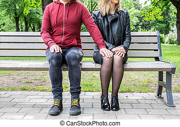 Couple sitting on a bench, man holding hand on knee of woman