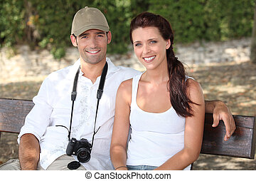 Couple sitting on a bench with a camera