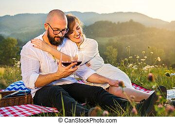 Couple sitting on a picnic blanket with wine glasses